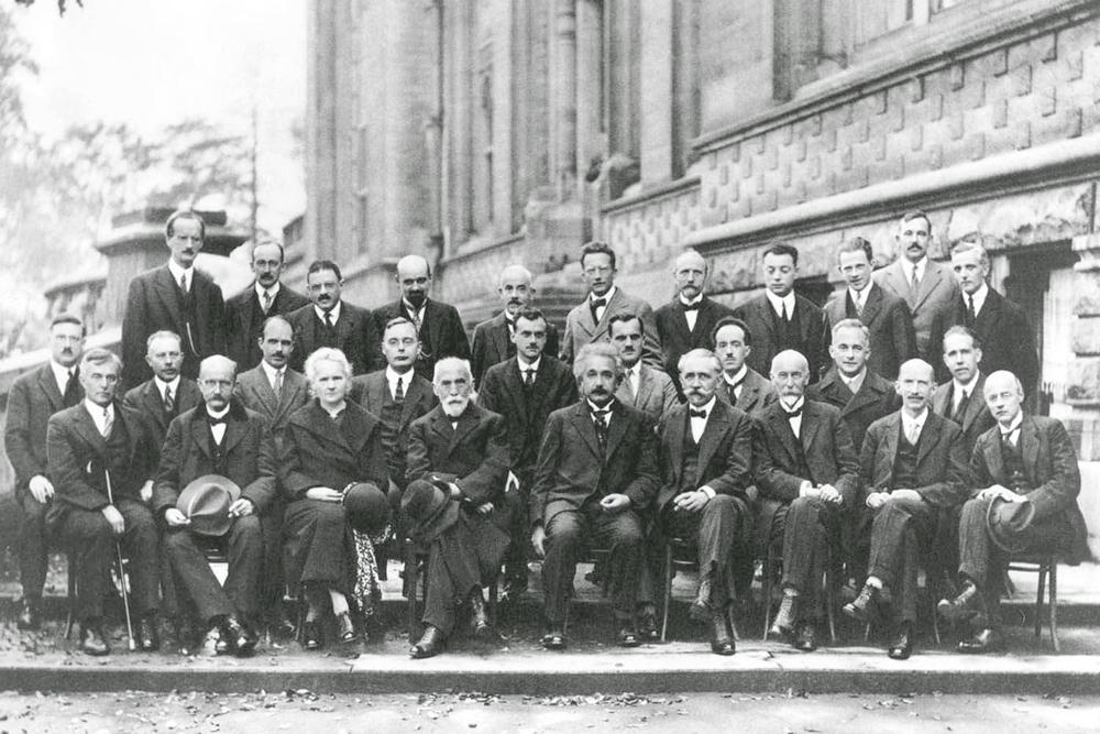 Слева направо, нижний ряд: Ирвинг Ленгмюр (Нобелевская премия по химии, 1932 - далее НПХ; по физике - НПФ), Макс Планк (НПФ-1918), Мария Кюри (НПФ-1903, НПХ-1911), Хенрик Лоренц (НПФ-1902), Альберт Эйнштейн (НПФ-1921), Поль Ланжевен, Шарль Гюи, Чарльз Вильсон (НПФ-1927), Оуэн Ричардсон (НПФ-1928). Средний ряд: Петер Дебай (НПХ-1936), Мартин Кнудсен, Уильям Брэгг (НПФ-1925), Хендрик Крамерс, Поль Дирак (НПФ-1933), Артур Комптон (НПФ-1927), Луи де Бройль (НПФ-1929), Макс Борн (НПФ-1954), Нильс Бор (НПФ-1922). Верхний ряд: Огюст Пикар (без «нобелевки», зато с изобретением батискафа «Трест», спустившегося на дно Мариинской впадины), Эмиль Анрио, Пауль Эренферст, Эдуард Герцен, Теофил де Дондер, Эрвин Шрёдингер (НПФ-1933), Жюль Эмиль Вершафельт, Вольфганг Паули (НПФ-1945), Вернер Гейзенберг (НПФ-1932), Ральф Фаулер, Леон Бриллюэн.